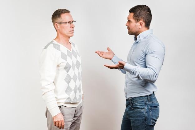 Medium shot vader en zoon praten