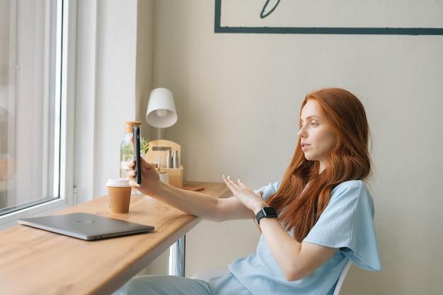Medium shot van aantrekkelijke jonge vrouw video-oproep op smartphone koffie drinken zittend aan tafel met laptop bij raam in café. mooie roodharige blanke dame met vrijetijdsbesteding in de coffeeshop.