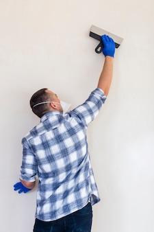 Medium shot van een man die aan een muur werkt