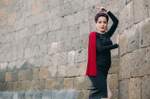 Medium shot van mooie en aantrekkelijke vrouw met rode mantel poserend naast het oude kasteel