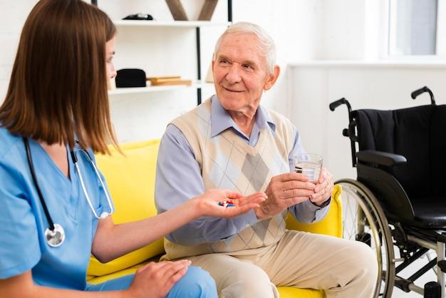 Medium shot verpleegster die een oude man zijn pillen geeft