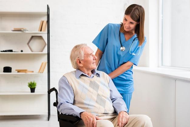 Medium shot verpleegster kijken naar oude man