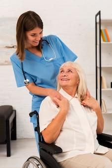 Medium shot verzorger en oude vrouw kijken naar elkaar