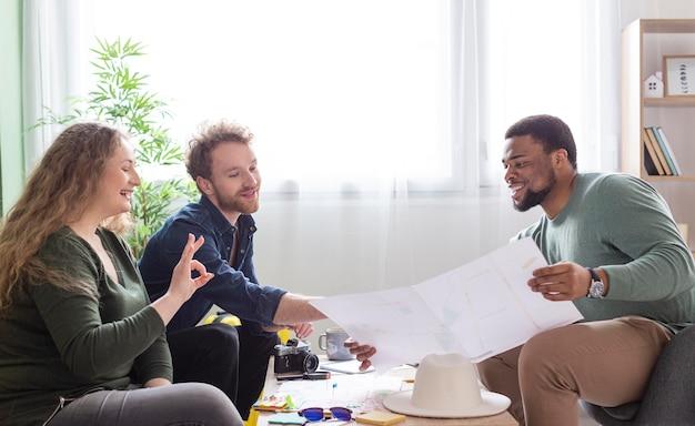 Medium shot vrienden die een reis aan tafel plannen