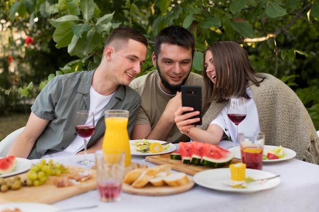 Medium shot vrienden die naar de telefoon kijken