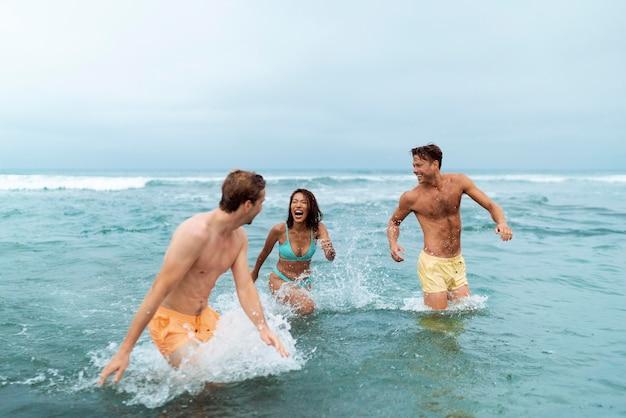 Medium shot vrienden die plezier hebben aan zee