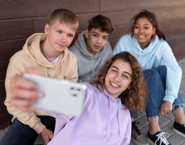 Medium shot vrienden die selfie buitenshuis nemen