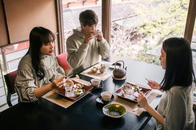Medium shot vrienden die van een maaltijd genieten