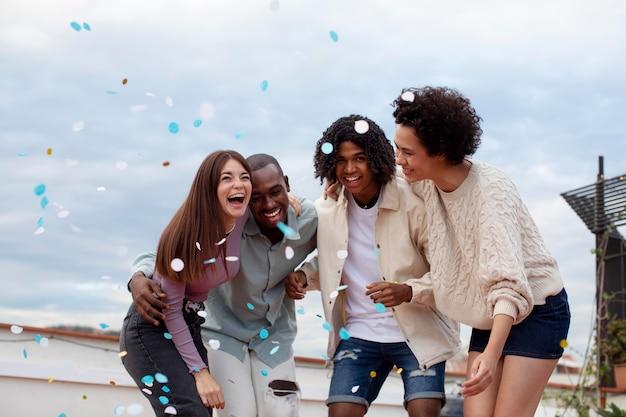 Medium shot vrienden feesten met confetti