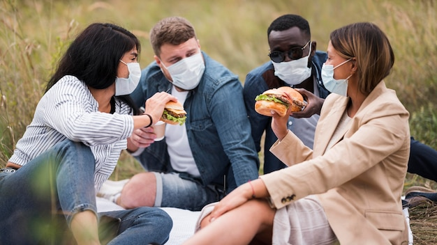 Medium shot vrienden met hamburgers en maskers