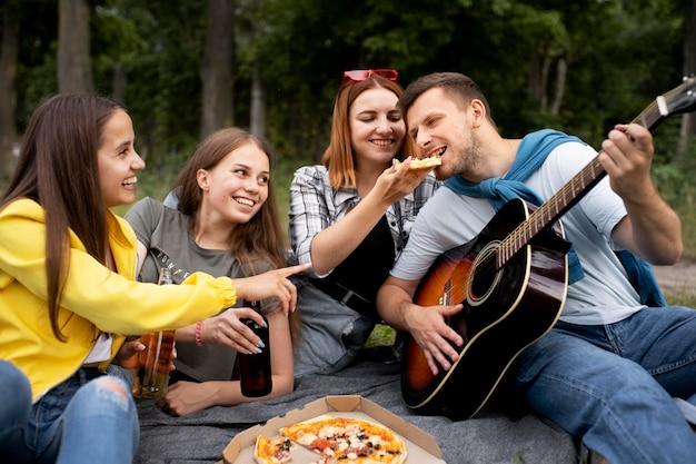 Medium shot vrienden met muziek en pizza