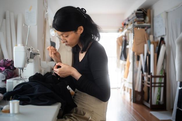 Medium shot vrouw aan het naaien