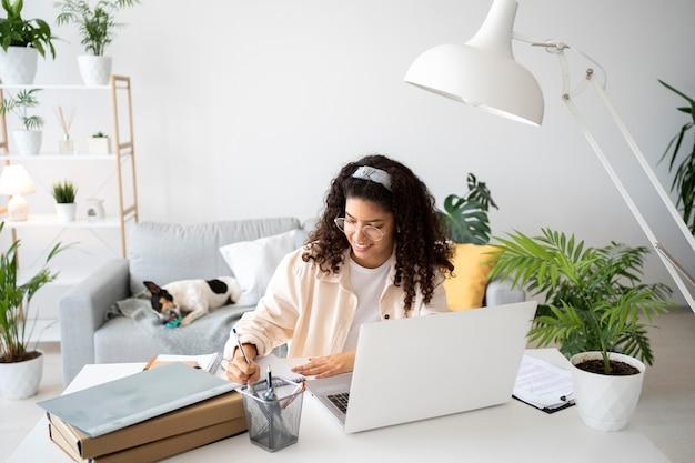 Medium shot vrouw die aan het bureau werkt met laptop
