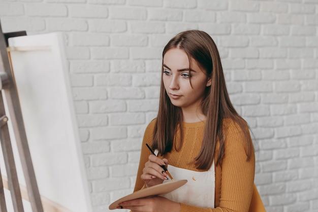 Medium shot vrouw die naar canvas kijkt