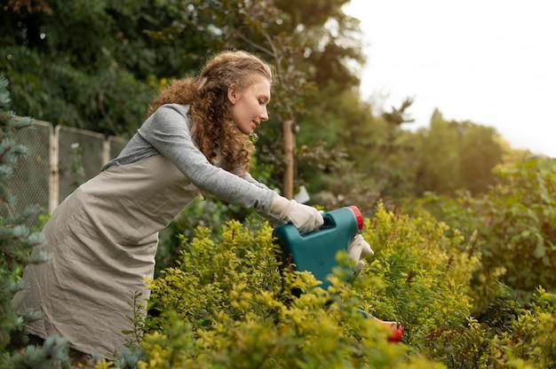 Medium shot vrouw die planten water geeft