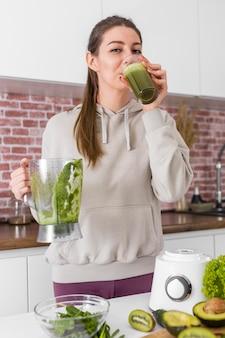 Medium shot vrouw die smoothie drinkt