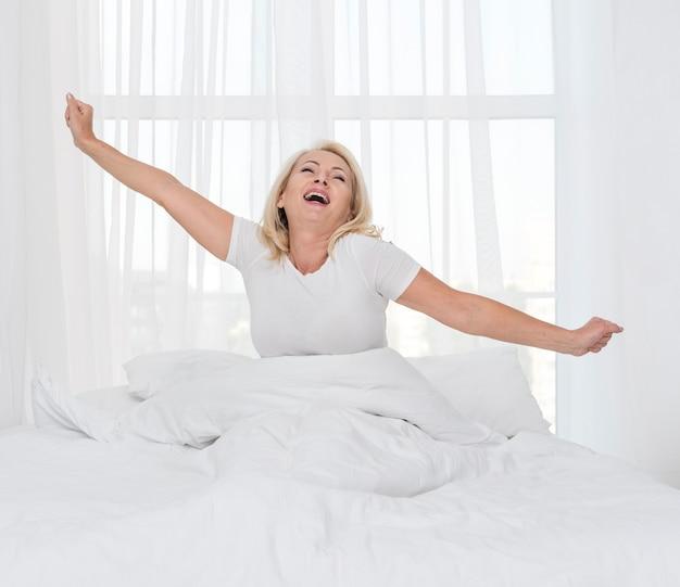 Medium shot vrouw die zich uitstrekt in de ochtend