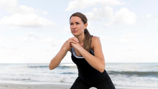 Medium shot vrouw die zich uitstrekt op het strand