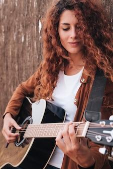 Medium shot vrouw gitaarspelen