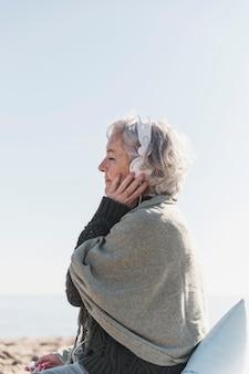 Medium shot vrouw luisteren naar muziek in de natuur