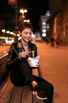 Medium shot vrouw met eten op de bank