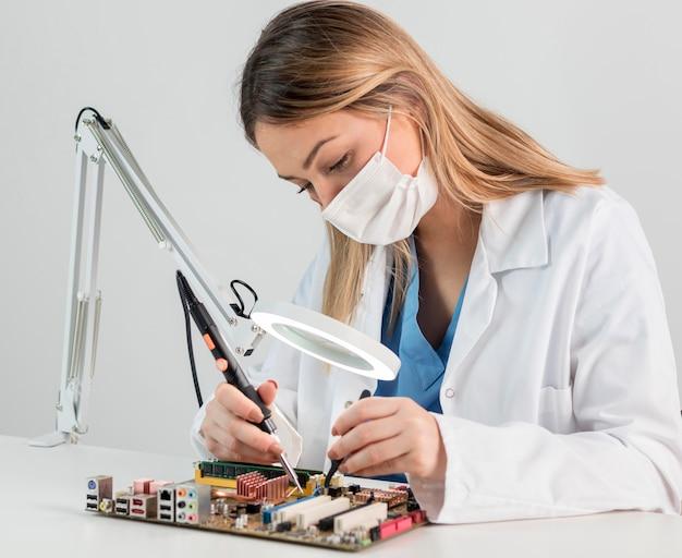 Medium shot vrouw met gezichtsmasker aan het werk