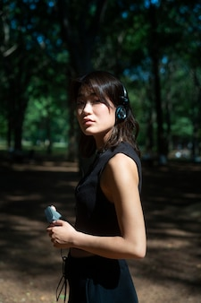 Medium shot vrouw met koptelefoon op
