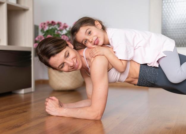 Medium shot vrouw met meisje op rug Gratis Foto