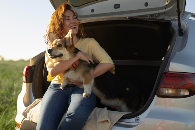 Medium shot vrouw met schattige hond en auto