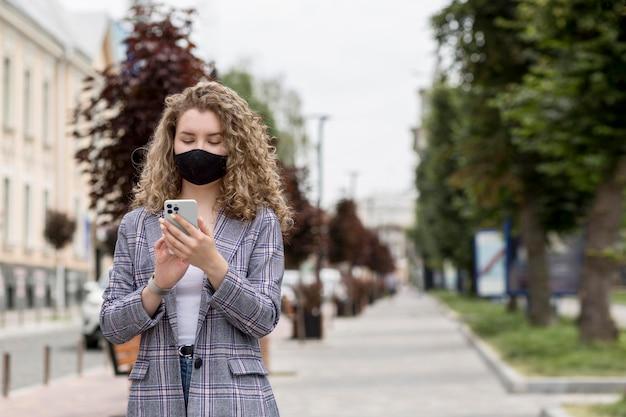 Medium shot vrouw met telefoon buitenshuis