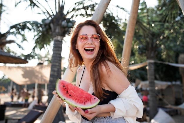 Medium shot vrouw met watermeloenplakje