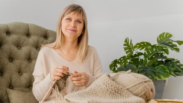 Medium shot vrouw op fauteuil breien