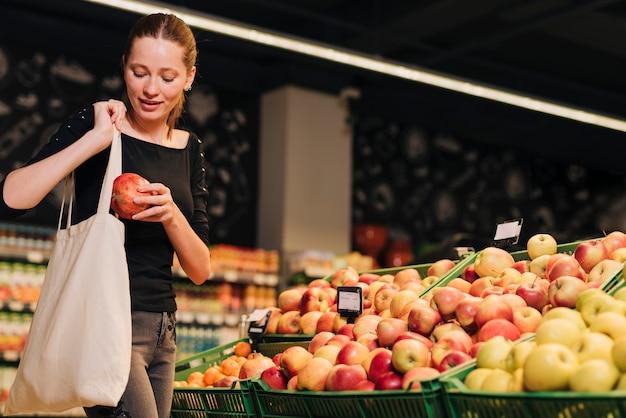 Medium shot vrouw winkelen voor granaatappel