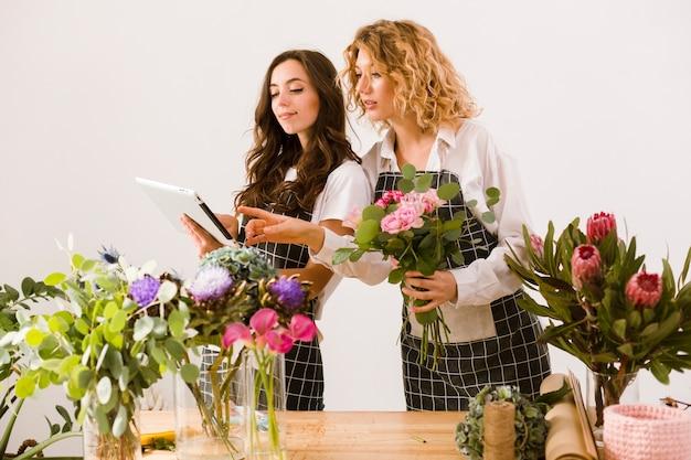 Medium shot vrouwen die werken bij bloemenwinkel