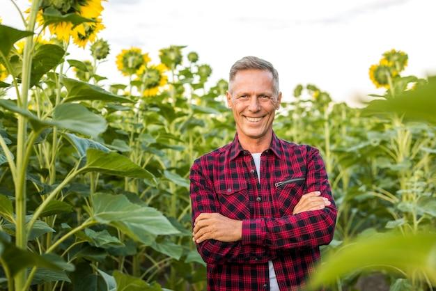 Medium weergave man op een veld met zonnebloemen