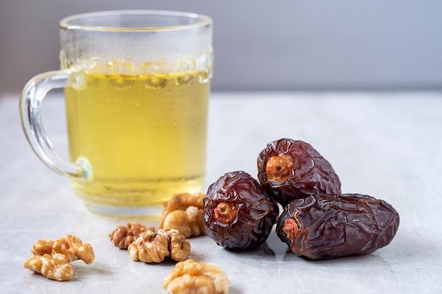 Medjool dadels met walnoten en thee op tafel. zeer voedzaam fruit verhoogt de moedermelk voor moeders die borstvoeding geven. in de volksmond gegeten in de maand ramadan. Premium Foto