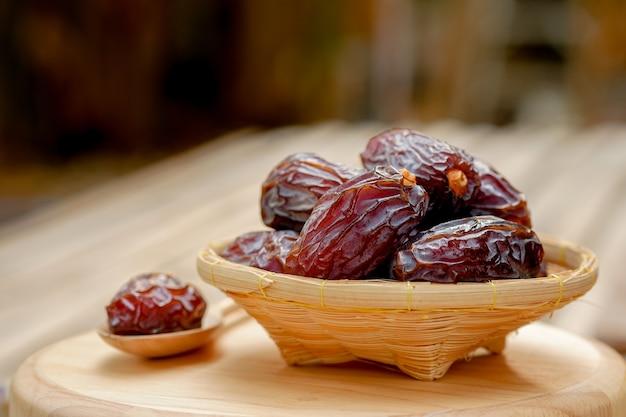 Medjool dadels of dadels fruit in houten mand en lepel op tafel