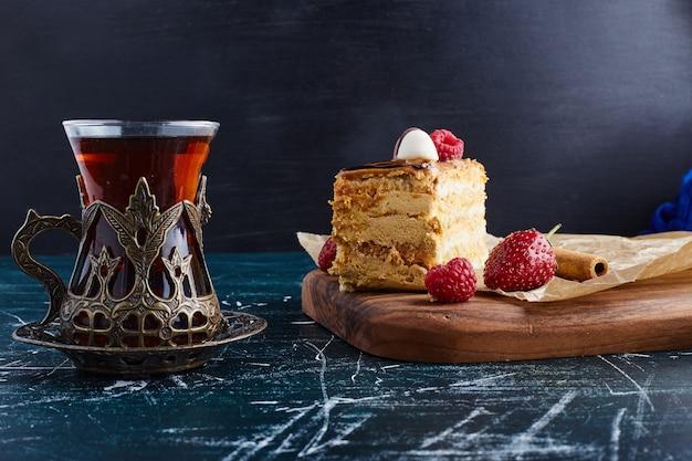 Medovic cake geserveerd met een glas thee op een houten bord.
