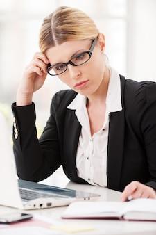Meedenken over oplossingen. doordachte volwassen vrouw in formele kleding die het hoofd in de hand houdt terwijl ze op haar werkplek zit