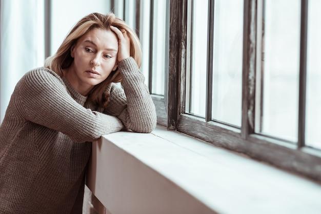 Meedenkend voelen. aangename rijpe vrouw die zich attent voelt met enkele persoonlijke problemen