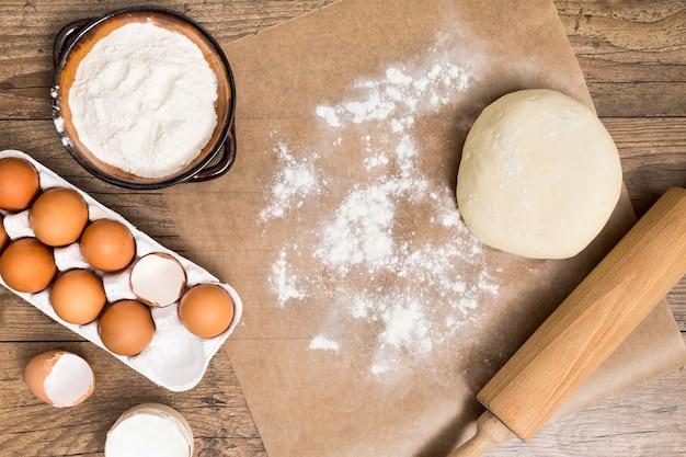 Meel; eierdoos; deeg; deegroller op perkamentpapier over het houten bureau
