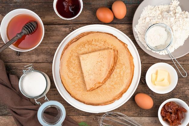Meel, eieren, honing, suiker en een stapel gebakken pannenkoeken op een bruine achtergrond.