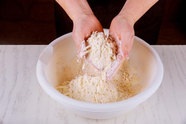 Meel en boter met handen wrijven voor het maken van koekjesdeeg.