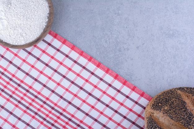 Meel en een met sesam bedekt brood tegenover elkaar op een marmeren oppervlak