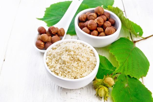 Meel en hazelnoten in twee kommen, een lepel met gepelde walnotenpitten en een tak van hazelnoot met bladeren op de achtergrond van een licht houten bord