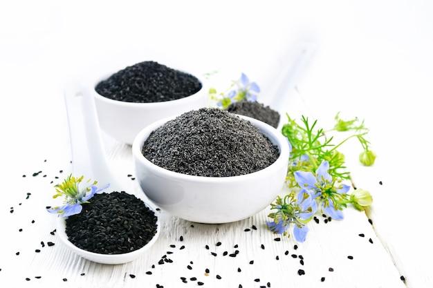 Meel en zaden van zwarte karwij in kommen, takjes kalingini met blauwe bloemen en groene bladeren op een houten plankachtergrond
