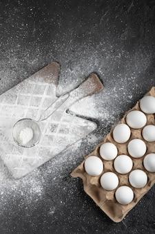Meel gemorst op een houten bord en rauwe eieren op een zwarte ondergrond