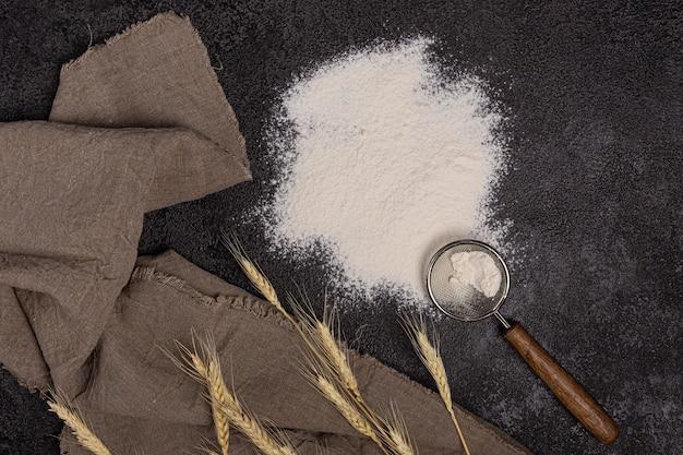 Meel in een bord met een bloemlepel. de textuur van de zwarte achtergrond. oren van tarwe