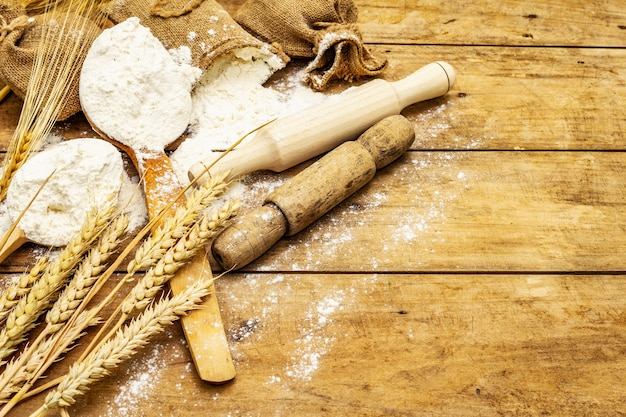Meel in zakken, korenaren, lepels en houten deegrollen. bakken concept, houten tafel, kopie ruimte