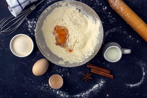 Meel met ei in een metalen kom tussen ingrediënten en keukengerei voor het koken van cake (meel, ei, melk, suiker, deegroller, handdoek) op donkere tafel. het concept van het maken van deeg voor het bakken. detailopname